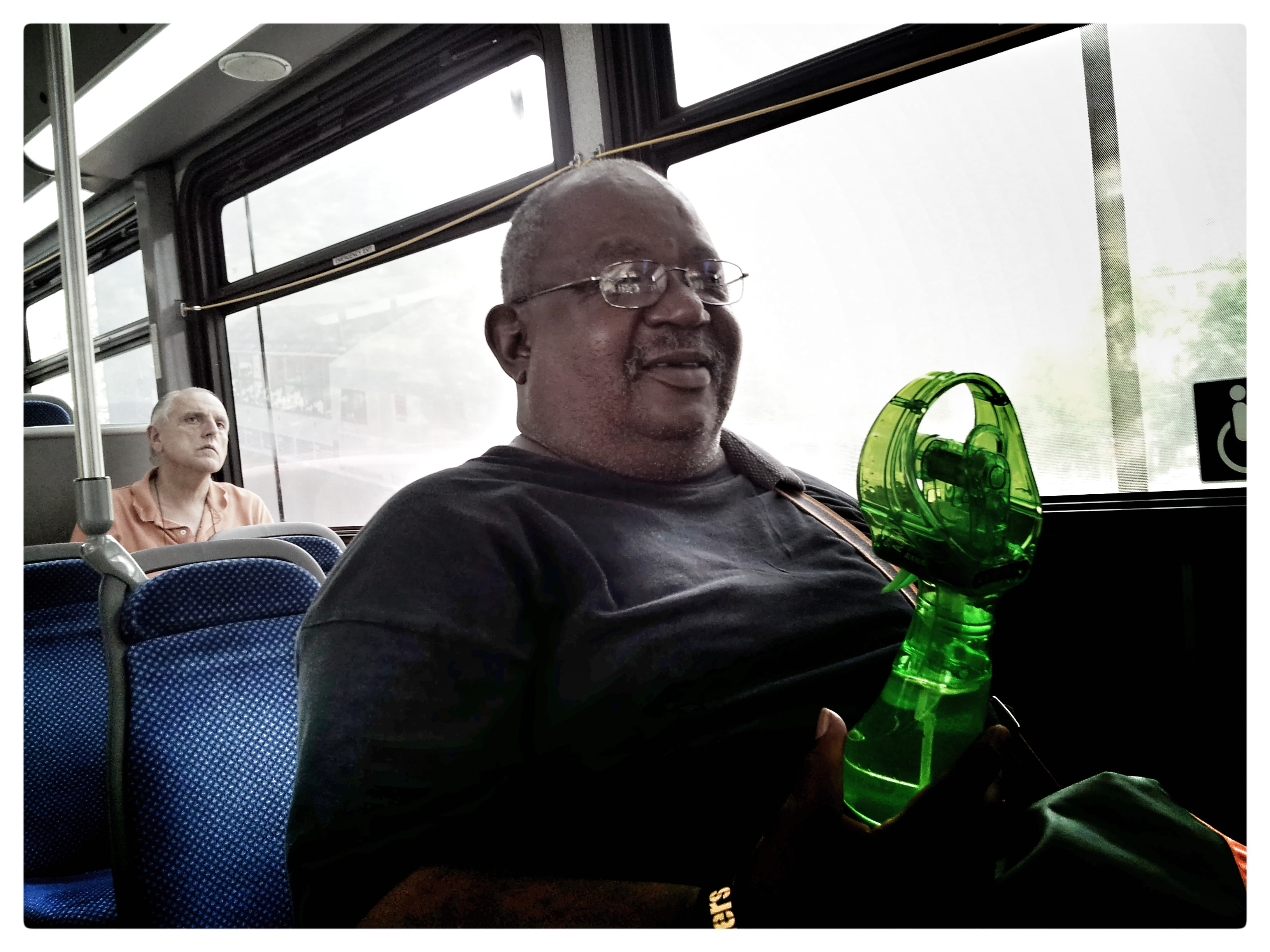 Anthony uses a personal hand-held battery-operated misting fan to stay cool - on his corner and on the 42 bus!